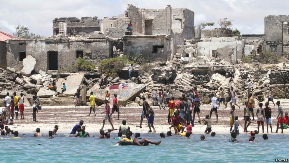 On-the-same-day-Mogadishu-residents-swim-at-Lido-beach-surrounded-by-buildings-scarred-by-Somalia's-two-decade-civil-war.-The-AU-and-Somali-government-army-drove-Islamist-militants-from-the-capital-more-than-a-year-a